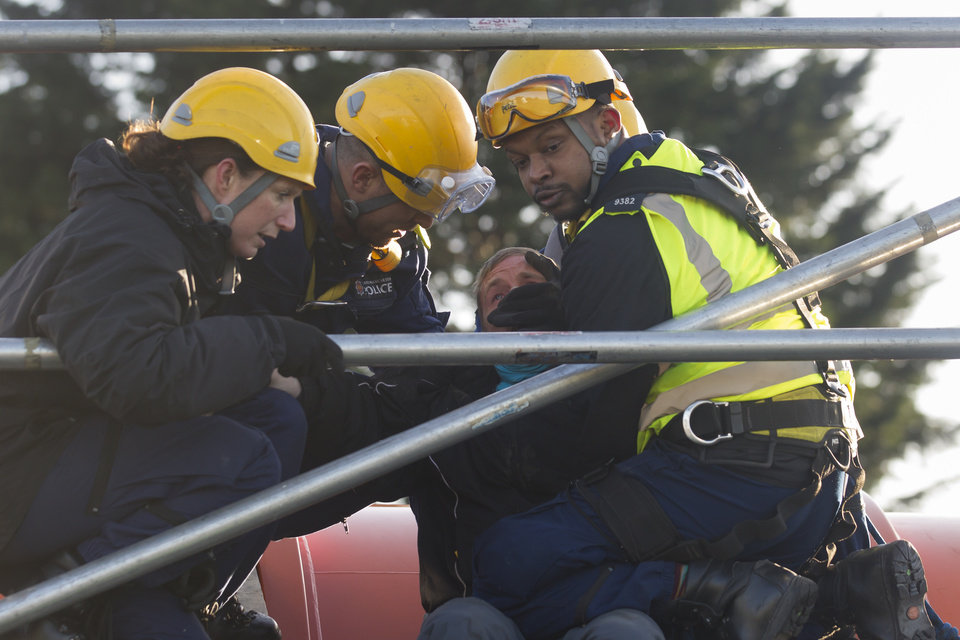 Photo - An anti-fracking protestor is removed from the top of a vehicle attempting to enter an exploratory drill site for the controversial gas extraction process at Barton Moss in Manchester, England, Monday, Jan. 13, 2014. Councils that back