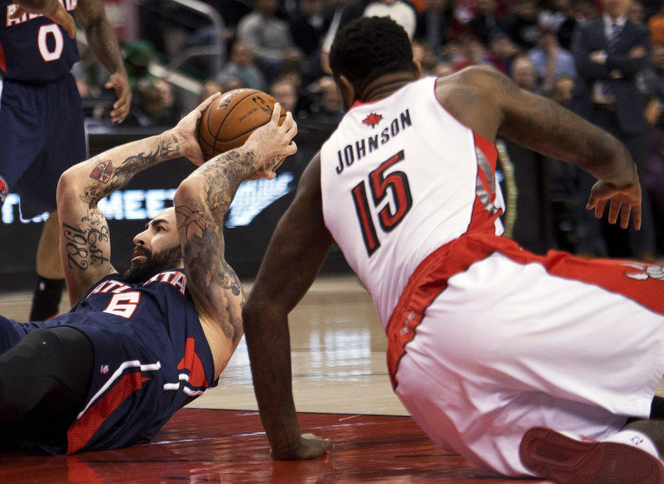 Photo - Toronto Raptors forward Amir Johnson (15) battles for the ball against Atlanta Hawks forward Pero Antic, left, during the first half of an NBA basketball game in Toronto on Sunday, March 23, 2014. (AP Photo/The Canadian Press, Nathan Denette)