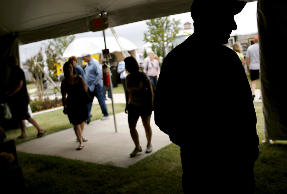 Visitors walk into tents and along sidewalks outside to look at artwork during the 2011 Arts Festival Oklahoma at Oklahoma City Community College. The 2012 festival continues through Monday at OCCC. Photo by John Clanton, The Oklahoman Archives. <strong>JOHN CLANTON - John Clanton</strong>