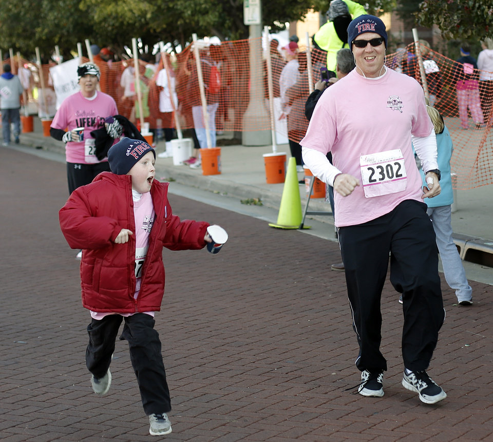 Larry Young, of Oklahoma City, and his son, Jake, 7, cross the finish line during the 19th Annual Oklahoma City Race for the Cure at Chicasaw Bricktown Ballpark in Oklahoma City, Saturday, Oct. 27, 2012.  Photo by Garett Fisbeck, The Oklahoman