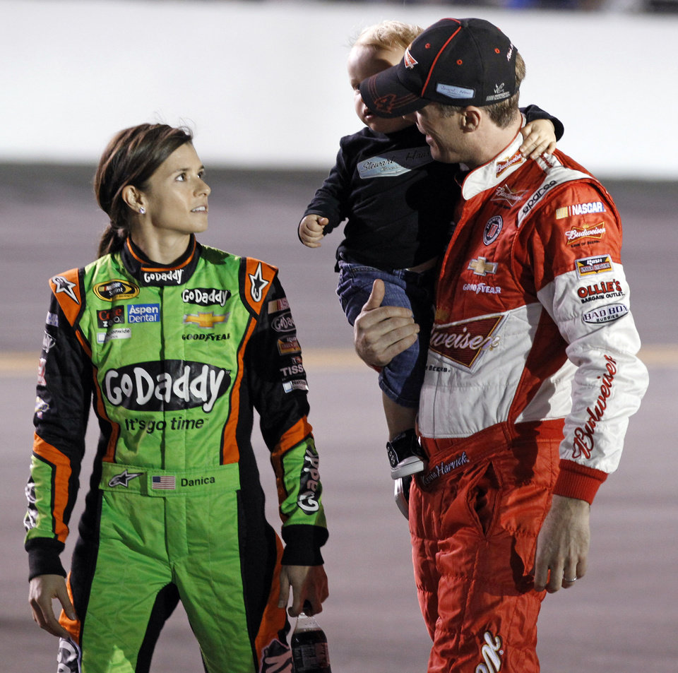 Photo - Danica Patrick, left, talks with Kevin Harvick before the first of two NASCAR Sprint Cup series qualifying auto races in Daytona Beach, Fla., Thursday, Feb. 20, 2014. (AP Photo/Terry Renna)