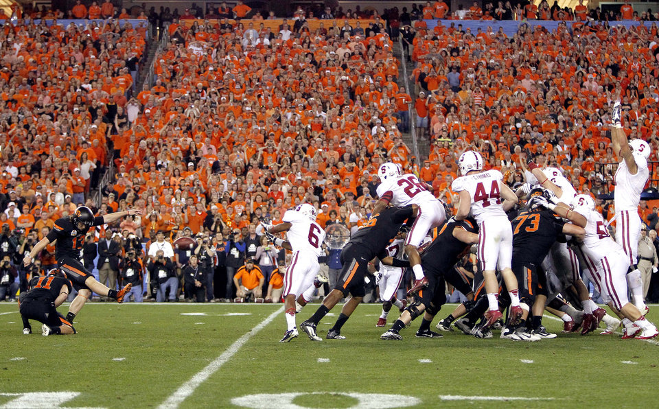 Oklahoma State kicker Quinn Sharp (13) kicks the game-winning field goal as teammate Wes Harlan (11) holds against Stanford during overtime of the Fiesta Bowl NCAA college football game, Monday, Jan. 2, 2012, in Glendale, Ariz. Oklahoma State won 41-38. (AP Photo/Matt York) ORG XMIT: PNP140