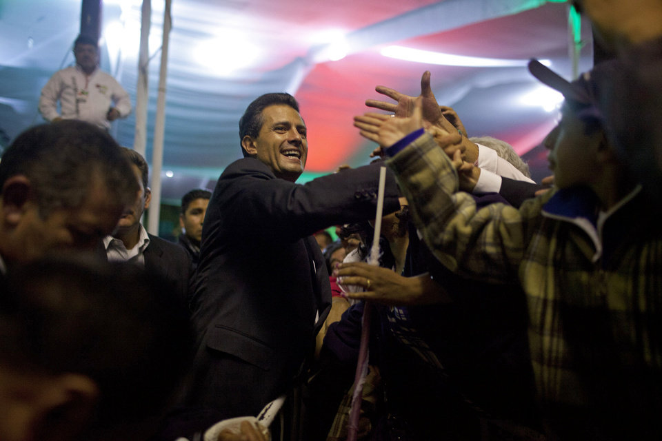Photo -   Enrique Pena Nieto, presidential candidate for the Revolutionary Institutional Party (PRI), center, greets supporters at the party's headquarters in Mexico City, early Monday July 2, 2012. Mexico's old guard sailed back into power after a 12-year hiatus Sunday as the official preliminary vote count handed a victory to Pena Nieto, whose party was long accused of ruling the country through corruption and patronage. (AP Photo/Alexandre Meneghini)