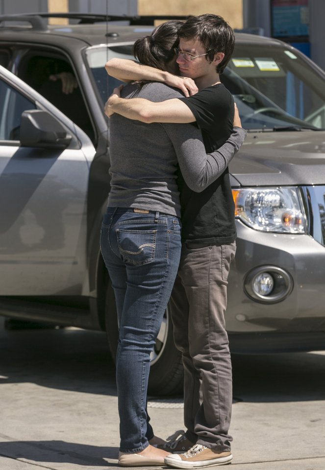 Miriam Arellano hugs her boyfriend, Eli Labinger, after being separated during a mandatory evacuation at the Cal State University Los Angeles after a mandatory evacuation by school authorities on a report of a suspicious item, according to police in Los Angeles Thursday, April 18, 2013. Two telephoned bomb threats prompted officials at Cal State Los Angeles today to cancel afternoon classes and evacuate the campus. (AP Photo/Damian Dovarganes)