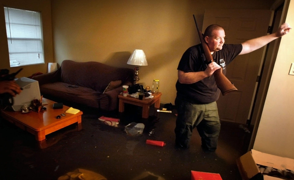 Photo - Knee deep in flood water, Crittenden County Arkansas Sheriff Deputy Darryn Richardson wades through his apartment to retrieve his hunting rifles Wednesday, April 27, 2011 at the Riverbend Apartment complex in West Memphis, Ark., where most of the ground-floor units were flooded by storm runoff. West Memphis was declared a disaster area by the state as rains continued to pound the midsouth causing low lying areas to flood after a night of high winds toppled trees and damaged businesses. (AP Photo/The Commercial Appeal, Jim Weber)