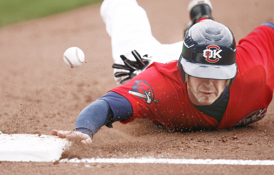 Photo - The Redhawks' Casey Benjamin dives back to first base during Sunday's game.  Photo by Sarah Phipps, The Oklahoman