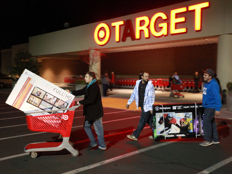 "Trevor Anderson, Mike Van Lone, and Zack McElwain (left to right) walk out with the televisions they purchased at Target, which opened at 9 p.m. as shoppers took advantage of the sales and deals in the earlier shopping period for the typical ""Black Friday"" event on Thursday evening, Nov. 22, 2012 in Chico, Calif. (AP Photo/Jason Halley, Chico Enterprise-Record)"