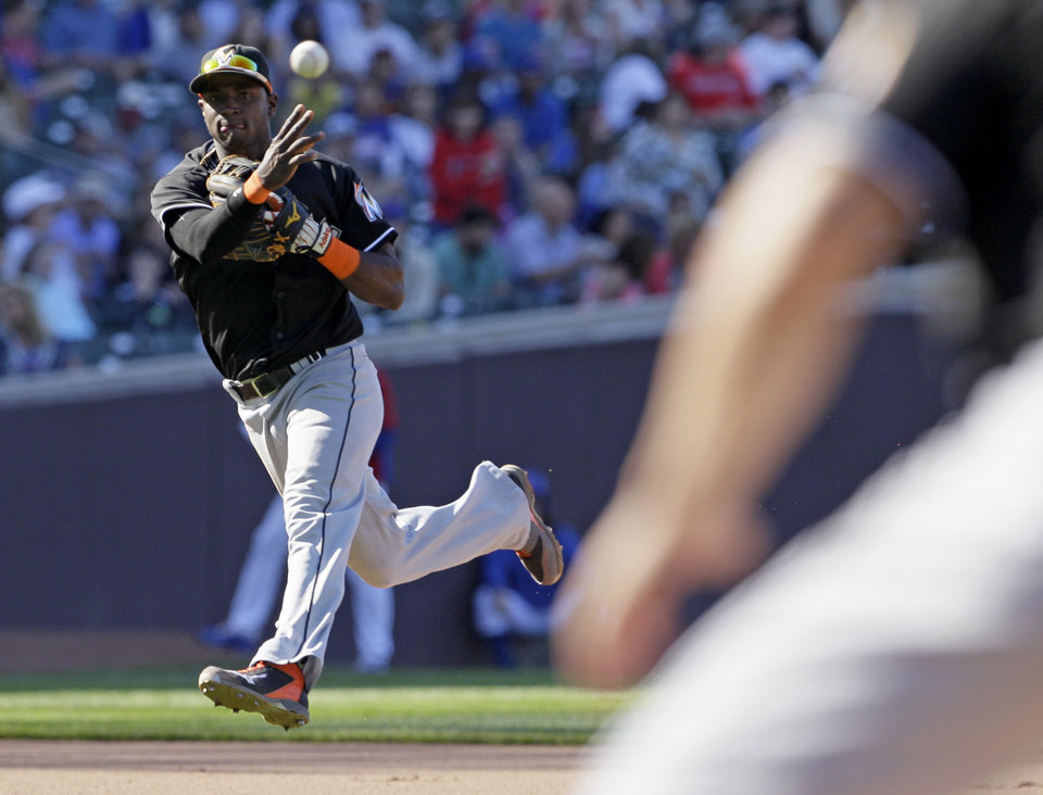 Photo - Miami Marlins shortstop Adeiny Hechavarria throws out Chicago Cubs' Starlin Castro at first base during the seventh inning of a baseball game in Chicago, Friday, June 6, 2014. (AP Photo/Nam Y. Huh)