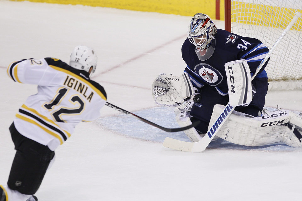 Photo - Winnipeg Jets'goaltender Michael Hutchinson (34) saves a breakaway shot from Boston Bruins' Jerome Iginla (12) during the first period of an NHL hockey game Thursday, April 10, 2014, in Winnipeg, Manitoba. (AP Photo/The Canadian Press, John Woods)