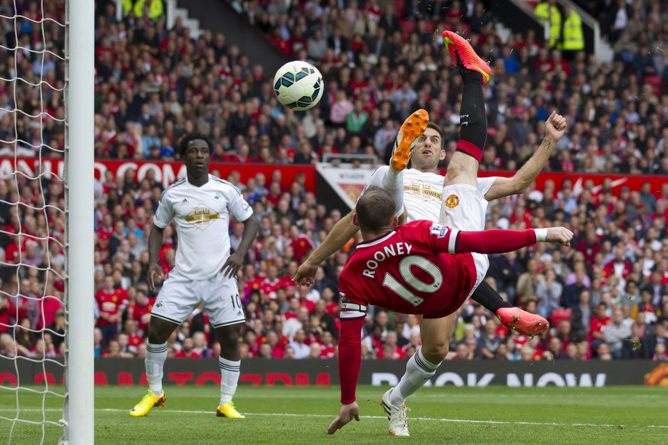 Photo - Manchester United's Wayne Rooney, right, scores against Swansea City during their English Premier League soccer match at Old Trafford Stadium, Manchester, England, Saturday Aug. 16, 2014. (AP Photo/Jon Super)