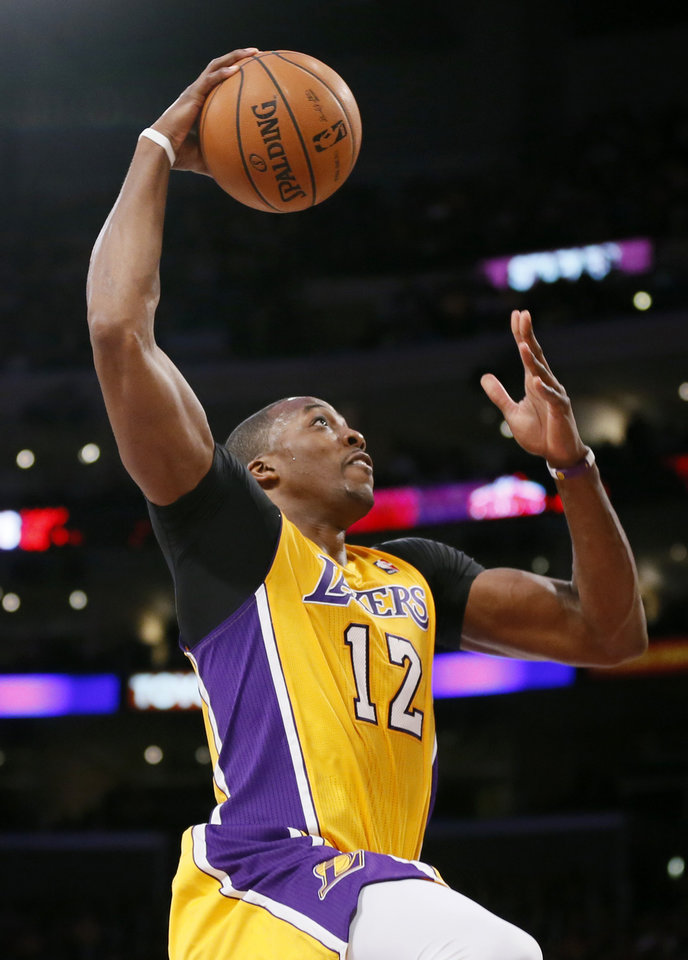 Photo - FILE - In this Feb. 12, 2013, file photo, Los Angeles Lakers' Dwight Howard goes up to dunk against the Phoenix Suns during the second half of an NBA basketball game in Los Angeles. Dallas Mavericks owner Mark Cuban tweeted Friday, July 5, 2013, that it was