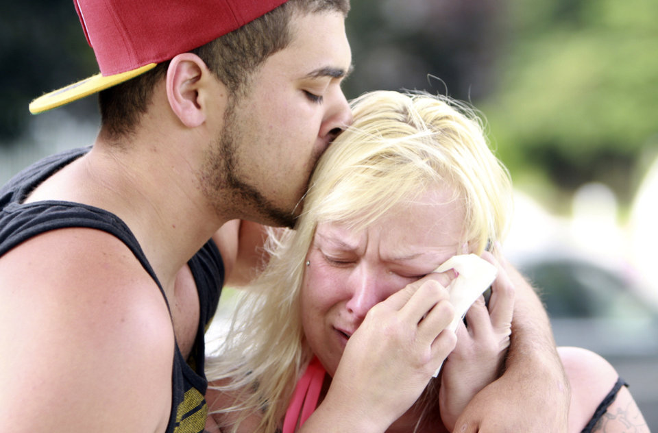 Photo - Two people comfort each other as they await word about the safety of students after a shooting at Reynolds High School Tuesday, June 10, 2014, in Troutdale, Ore. A gunman killed a student at the high school east of Portland Tuesday and the shooter is also dead, police said. (AP Photo/The Oregonian, Faith Cathcart)  MAGS OUT; TV OUT; LOCAL TV OUT; LOCAL INTERNET OUT; THE MERCURY OUT; WILLAMETTE WEEK OUT; PAMPLIN MEDIA GROUP OUT