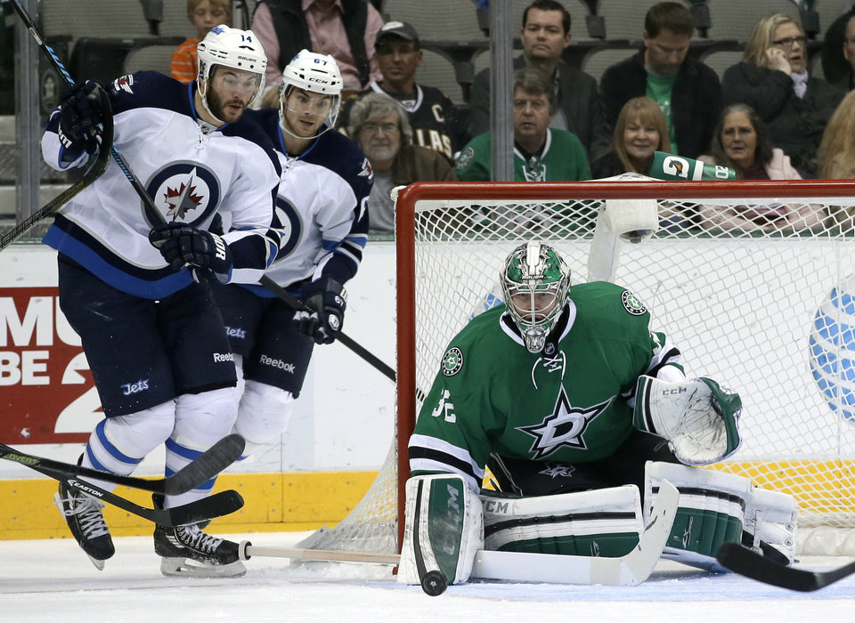 Photo - Dallas Stars goalie Kari Lehtonen (32), of Finland, blocks a shot as Winnipeg Jets right wing Anthony Peluso (14) and Michael Frolik (67), of Czech Republic, watch in the first period of an NHL hockey game, Saturday, Oct. 26, 2013, in Dallas. (AP Photo/Tony Gutierrez)