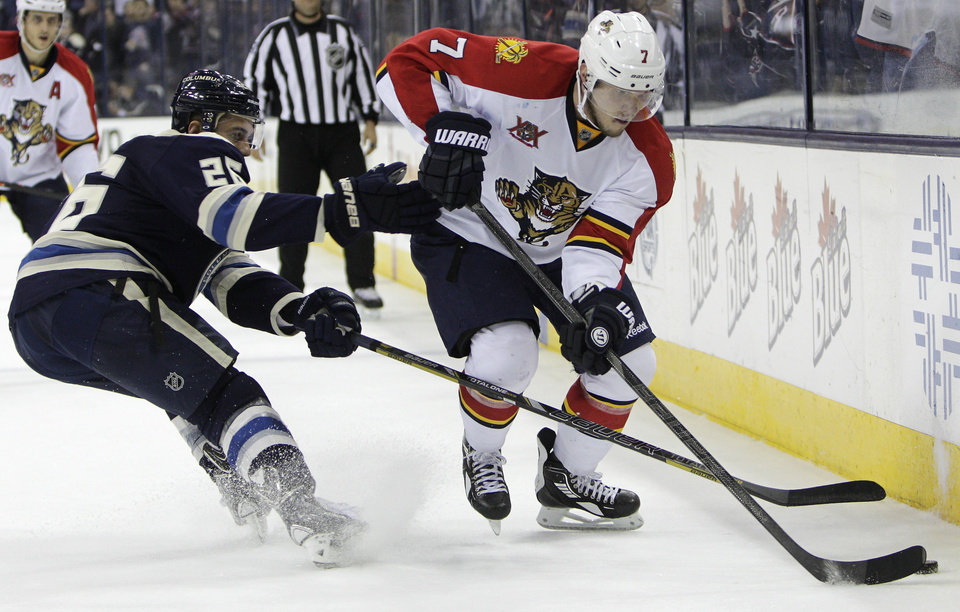 Photo - Florida Panthers' Dmitry Kulikov, right, tries to pass the puck past Columbus Blue Jackets' Corey Tropp during the third period of an NHL hockey game on Saturday, Feb. 1, 2014, in Columbus, Ohio. The Blue Jackets won 4-1. (AP Photo/Jay LaPrete)