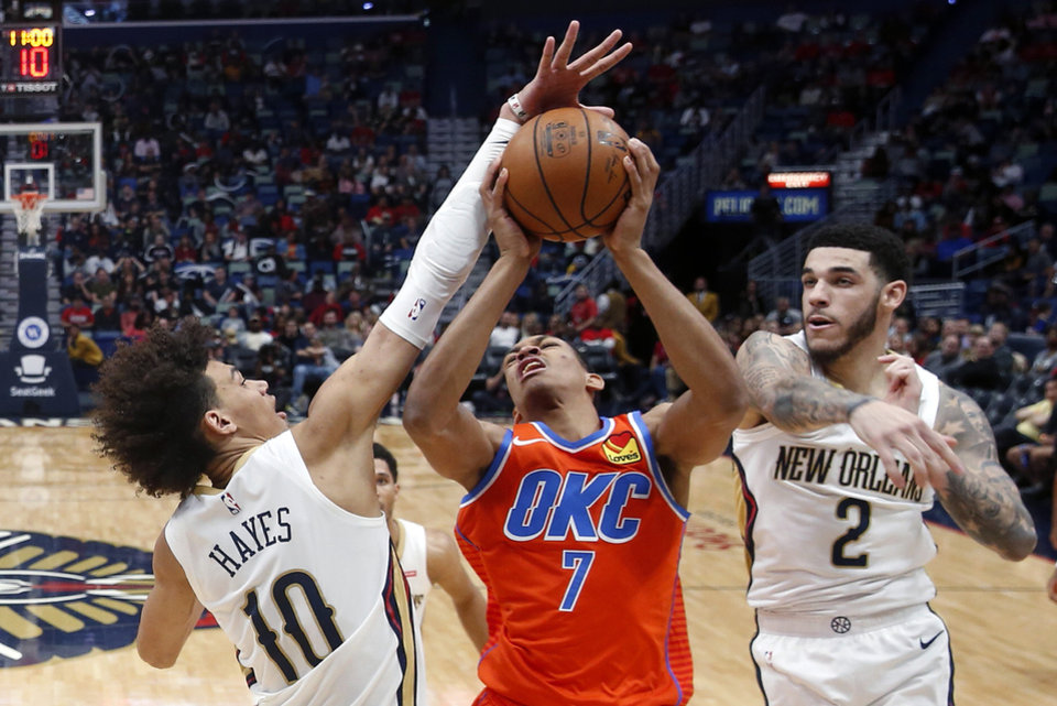 Photo - Oklahoma City Thunder forward Darius Bazley (7) is stopped as he drives to the basket between New Orleans Pelicans center Jaxson Hayes (10) and guard Lonzo Ball (2) in the second half of an NBA basketball game in New Orleans, Sunday, Dec. 1, 2019. The Thunder won 107-104. (AP Photo/Gerald Herbert)