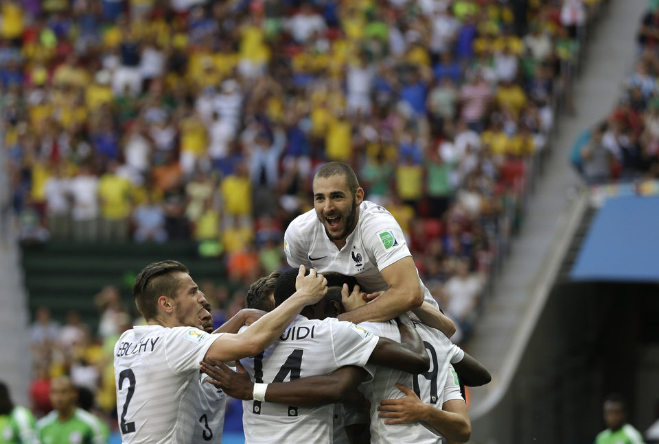 Photo - France's Karim Benzema, top, celebrates with teammates including Paul Pogba, bottom right, after Pogba scored their side's first goal during the World Cup round of 16 soccer match between France and Nigeria at the Estadio Nacional in Brasilia, Brazil, Monday, June 30, 2014. France won 2-0 to reach the World Cup quarterfinals. (AP Photo/Ricardo Mazalan)