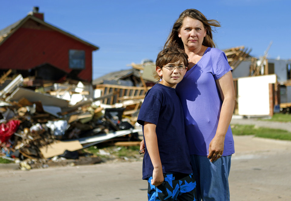 Karey Link and her son Gavin Cleary, 11, stand outside their neighbors home in Moore, Okla., on Tuesday, Jun11, 2013. Karey's home and her neighbors were damaged by the May 20 tornado that hit Moore and was offended by the actions of the tornado chasing tour company Extreme Tornado Tour. Photo by Bryan Terry, The Oklahoman