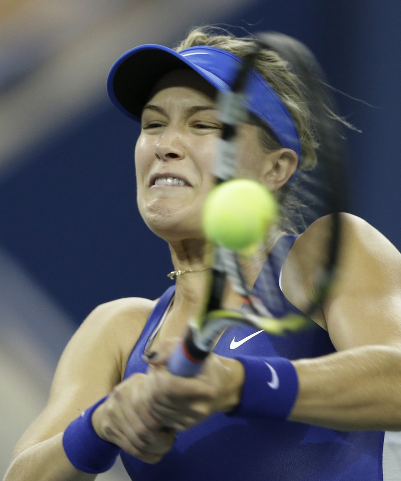Photo - Eugenie Bouchard, of Canada, returns a shot to Sorana Cirstea, of Romania, during the second round of the 2014 U.S. Open tennis tournament Thursday, Aug. 28, 2014, in New York. (AP Photo/Darron Cummings)