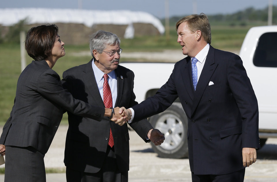 Photo - King Willem-Alexander of the Netherlands is greeted by Iowa Gov. Terry Branstad, center, and Iowa Lt. Gov. Kim Reynolds, left, while arriving at the opening of one of the nation's first commercial size cellulosic ethanol plants, Wednesday, Sept. 3, 2014, in Emmetsburg, Iowa. Project Liberty is a $250 million plant that will make 25 million gallons of ethanol a year from corn cobs, stalks, leaves and other plant residue. The project is a joint venture of Sioux Falls, South Dakota-based ethanol-maker POET and Royal DSM, a Netherlands biotechnology company. (AP Photo/Charlie Neibergall)