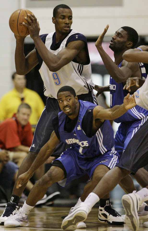 Photo - Oklahoma City Thunder's Serge Ibaka tries to pass around Dallas Mavericks' Aaron Miles, left, and Alfred Aboya during their NBA Summer League basketball game at Thomas & Mack Arena in Las Vegas on Saturday, July 18, 2009. (AP Photo/Laura Rauch) ORG XMIT: NVLR102
