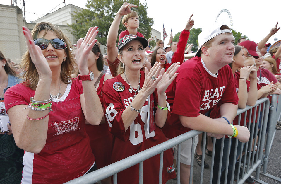 Photo - Sooner fans Elizabeth Woods, Stacy Irwin and Clayton Woods, from left, cheer on their team as the busses arrive at the stadium during the Red River Rivalry college football game between the University of Oklahoma (OU) and the University of Texas (UT) at the Cotton Bowl in Dallas, Saturday, Oct. 13, 2012. Photo by Chris Landsberger, The Oklahoman