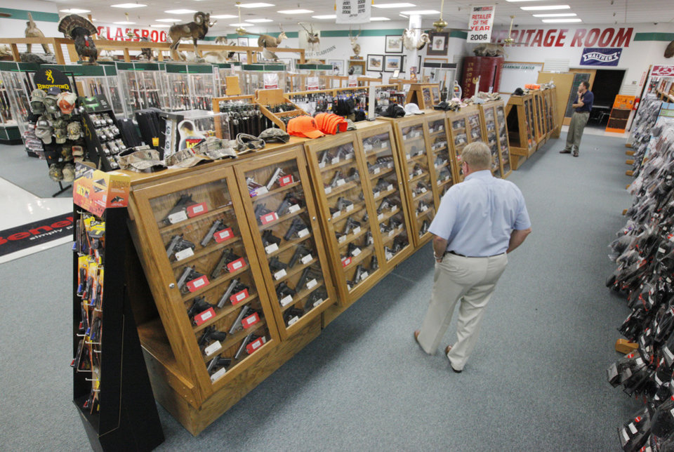 Photo - A customer looking at handguns for sale inside H & H Shooting Sports, 400 S Vermont, in Oklahoma City Wednesday, June 25, 2014.  Photo by Paul B. Southerland, The Oklahoman