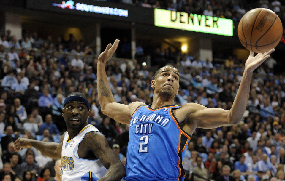 Photo - Oklahoma City Thunder guard Thabo Sefolosha (2) from Switzerland loses possession as Denver Nuggets guard Ty Lawson (3) looks on during the first half of game 3 of a first-round NBA basketball playoff series Saturday, April 23, 2011, in Denver. (AP Photo/Jack Dempsey)