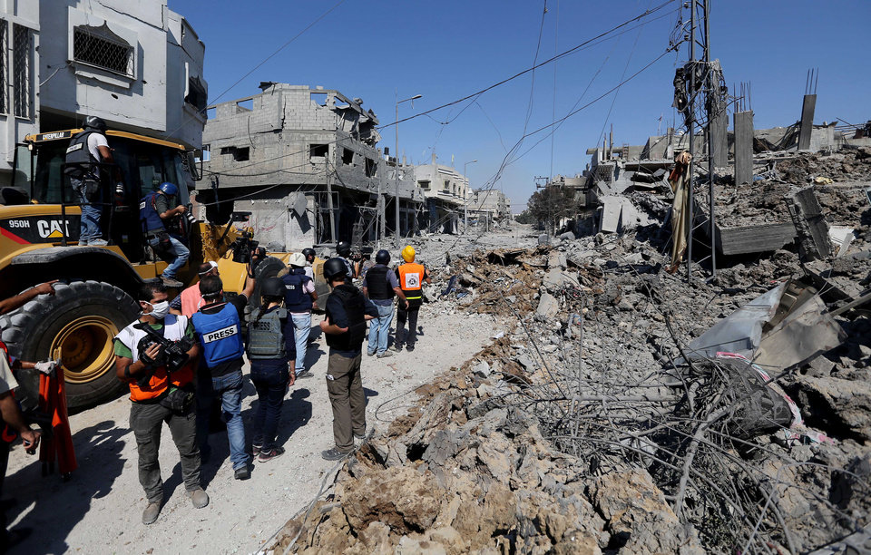 Photo - Palestinian rescuers search for the dead and injured in the rubble during a two hour temporary ceasefire in Gaza City's Shijaiyah neighborhood, Wednesday, July 23, 2014. sraeli troops battled Hamas militants on Wednesday near a southern Gaza Strip town as the top U.S. diplomat reported progress in efforts to end fighting that has so far killed more than 600 Palestinians and more than 30 Israelis. (AP Photo/Hatem Moussa)