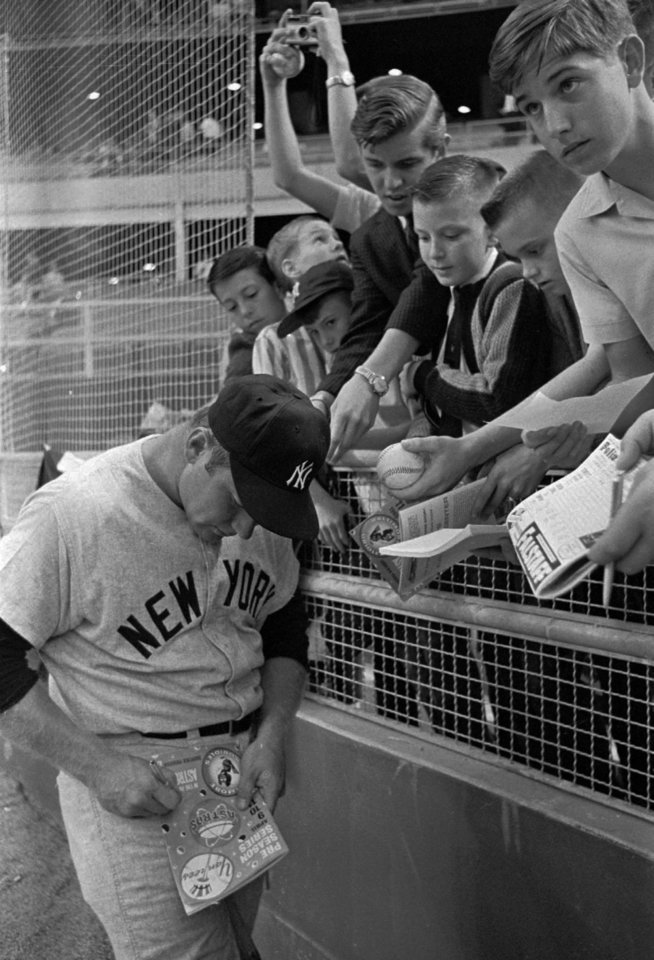 Photo - Mickey Mantle is surrounded by young fans in Houston in this 1965 file photo. Once Mickey Mantle's playing career ended, he moved into the role of being Mickey Mantle. He funded that lifestyle by autographing hundreds of thousands of items, each worth more and in higher demand following his death.(AP Photo/file)