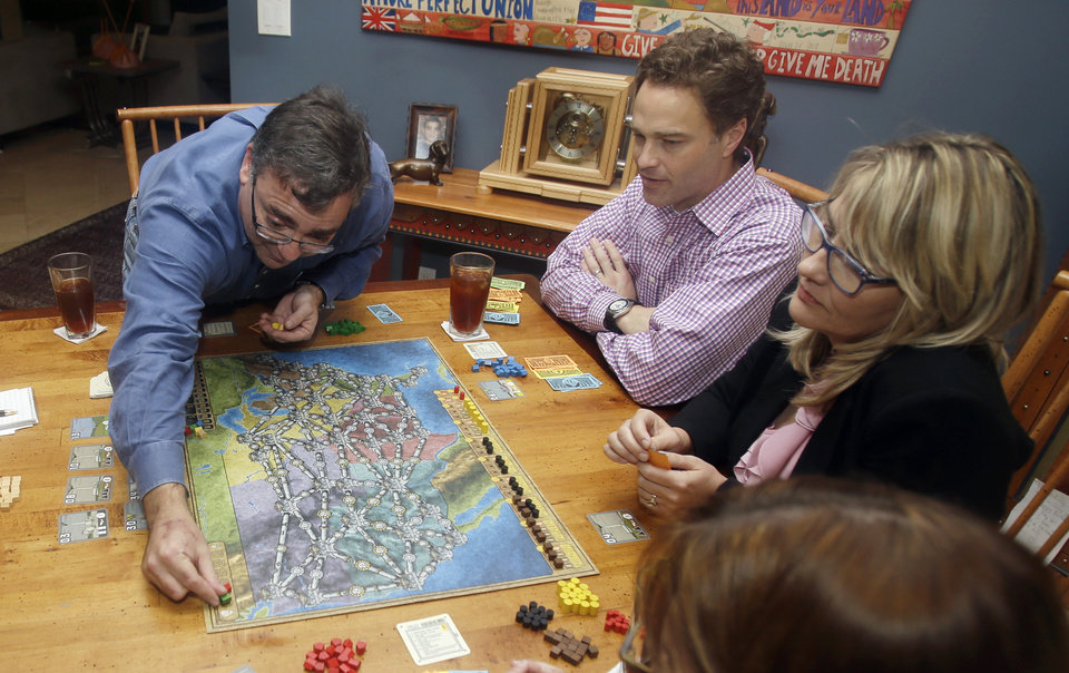 Photo - In this photo taken Thursday, Jan. 9, 2014, Spirit Airlines CEO Ben Baldanza left,  Ted Christie, center, the airline's chief financial officer,  and DeAnne Gabel,  right, director Investor relations, right, play a game of Power Grid at Baldanza's home, in Fort Lauderdale, Fla. (AP Photo/Alan Diaz)