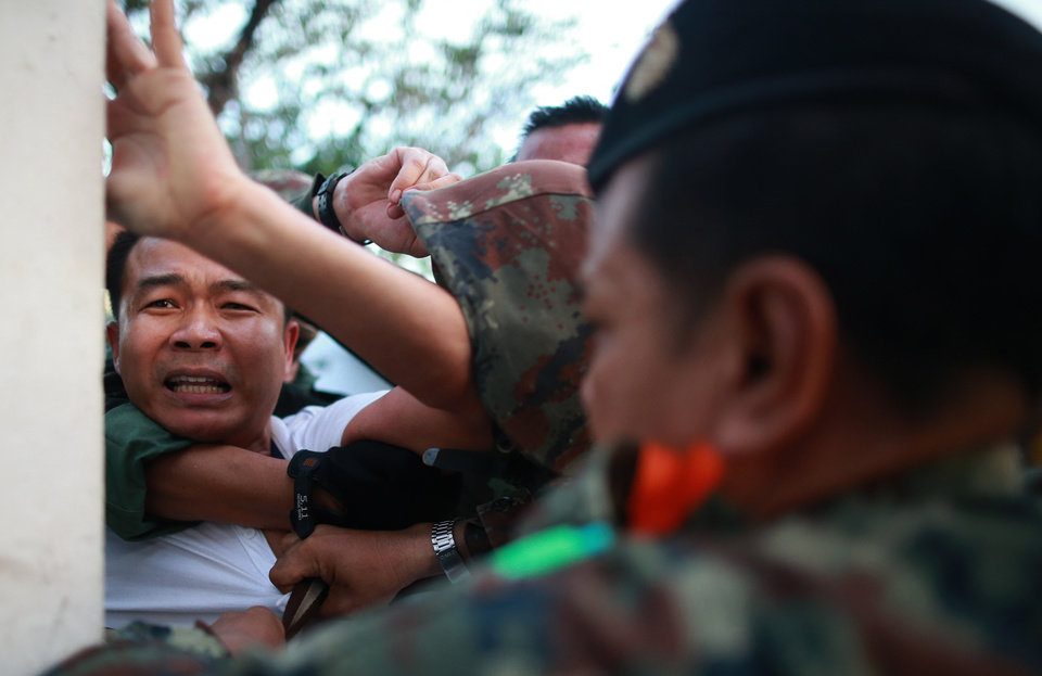 Photo - A protester, left, is detained by Thai soldiers during an anti-coup demonstration at the Victory Monument in Bangkok, Thailand Saturday, May 24, 2014. Thailand's coup leaders said Saturday that they would keep former Prime Minister Yingluck Shinawatra, Cabinet members and anti-government protest leaders detained for up to a week to give them