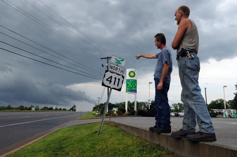 Photo - Jeff Madden, left, and David Covert watch as storm clouds pass  by Highway 411 in Vonore, Tenn., Wednesday, April 27, 2011. Powerful thunderstorms crossed the Mississippi River and pounded West Tennessee on Tuesday night and Wednesday morning, then barreled through Middle and East Tennessee. The storms downed power lines, flooded some residential streets, felled trees that blocked roads, and damaged buildings. (AP Photo/The Knoxville News Sentinel, Adam Brimer)