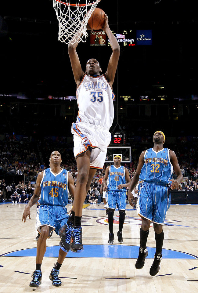 Photo - Oklahoma City's Kevin Durant dunks the ball past Rasual Butler, left, James Posey, and Julian Wright of New Orleans during the NBA basketball game between the Oklahoma City Thunder and the New Orleans Hornets at the Ford Center in Oklahoma City on Friday, Nov. 21, 2008.   BY BRYAN TERRY, THE OKLAHOMAN