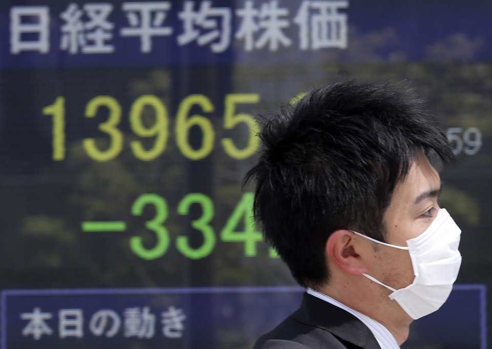 Photo - A man walks by an electronic stock board of a securities firm in Tokyo showing Japan's Nikkei 225 stock average that dropped 334 points to 13,965 Friday morning, April 11, 2014. (AP Photo/Koji Sasahara)