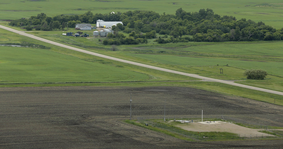 """Photo - This photo taken June 24, 2014, shows an ICBM launch site located among fields and farms in the countryside outside Minot, N.D., on the Minot Air Force Base. The nuclear missiles hidden in plain view across the prairies of northwest North Dakota reveal one reason why trouble keeps finding the nuclear Air Force. The """"Big Stick,"""" as some call the 60-foot-tall Minuteman 3 missile, is just plain old. (AP Photo/Charlie Riedel)"""