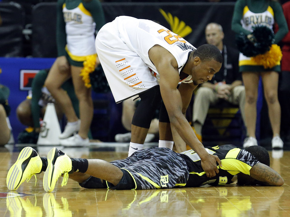 Photo - Oklahoma State's Markel Brown (22) tries to console Baylor's Pierre Jackson (55) after he missed a last-second shot during the Phillips 66 Big 12 Men's basketball championship tournament game between Oklahoma State University and Baylor at the Sprint Center in Kansas City, Thursday, March 14, 2013. Photo by Sarah Phipps, The Oklahoman