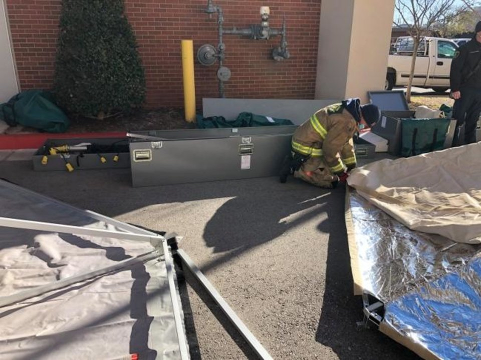 Photo -  Members of the OKCFD Urban Search and Rescue Team assist the Oklahoma City-County Health Department in assembling portable shelters on Monday for the possibility of overflow COVID patients. [Oklahoma City Fire Department]