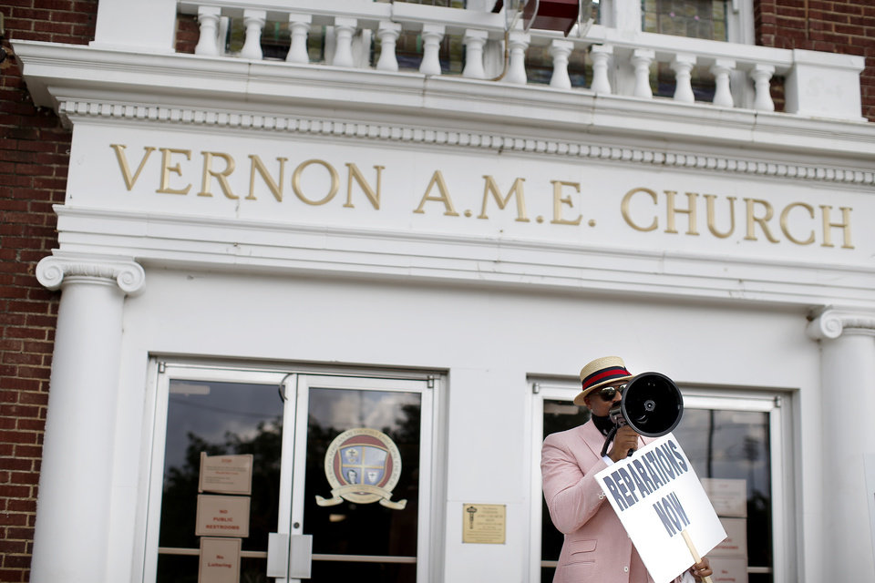 Photo -  The Rev. Robert Turner speaks to supporters on Wednesday outside at Vernon African Methodist Episcopal Church where he serves as senior pastor. [Sarah Phipps/The Oklahoman]