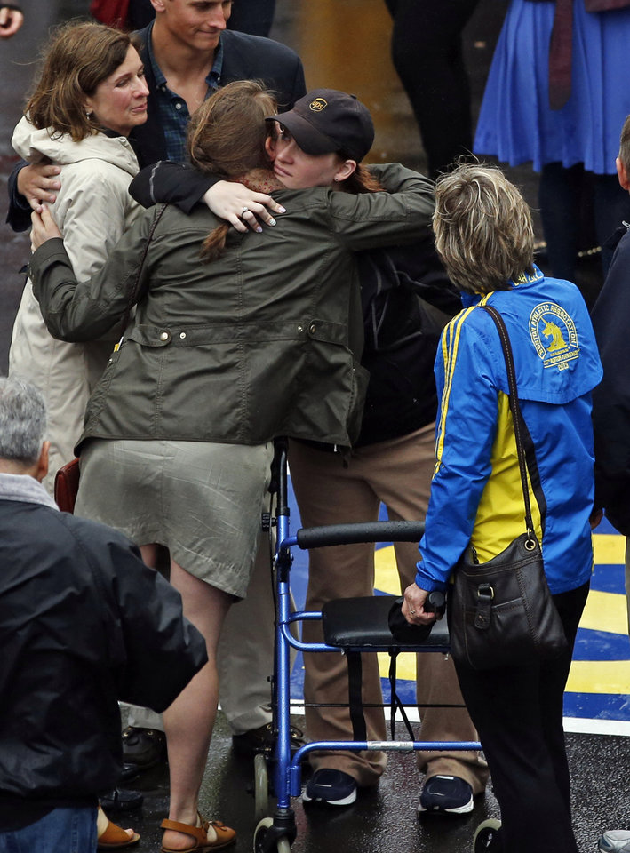 Photo - 2013 Boston Marathon bombing survivor Erika Brannock, a pre-school teacher from the Baltimore area, with hat, is hugged as her mother, Carol Downing, watches at right after a remembrance ceremony at the marathon finish line on Boylston Street in Boston, Tuesday, April 15, 2014. (AP Photo/Elise Amendola)