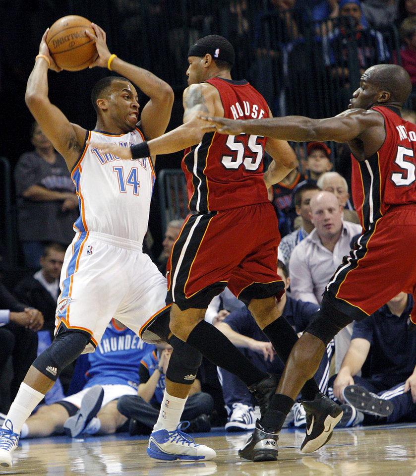 Photo - Oklahoma City's Daequan Cook is pressured by Miami's Eddie House and Joel Anthony during their NBA basketball game at the OKC Arena in Oklahoma City on Thursday, Jan. 30, 2011. Photo by John Clanton, The Oklahoman