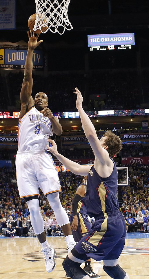 Photo - Oklahoma City's Serge Ibaka (9) shoots beside New Orleans' Omer Asik (3) during an NBA game between the Oklahoma City Thunder and the New Orleans Pelicans at Chesapeake Energy Arena on Friday, Feb. 6, 2015. Photo by Bryan Terry, The Oklahoman
