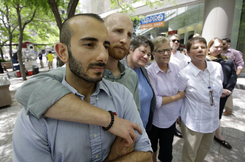 Photo - From left, plaintiffs Moudi Sbeity and Derek Kitchen, Kate Call, Laurie Wood and Kody Partridge, five of the six people who brought the lawsuit against the Utah's gay marriage ban, stand together at a news conference outside their lawyer's office Wednesday, June 25, 2014, in Salt Lake City. Call's partner, Karen Archer, was not able to attend. On Wednesday, June 25, 2014, a federal appeals court in Denver ruled that states must allow gay couples to marry, finding the Constitution protects same-sex relationships. The decision from a three-judge panel in Denver upheld a lower court ruling that struck down Utah's gay marriage ban. (AP Photo/Rick Bowmer)