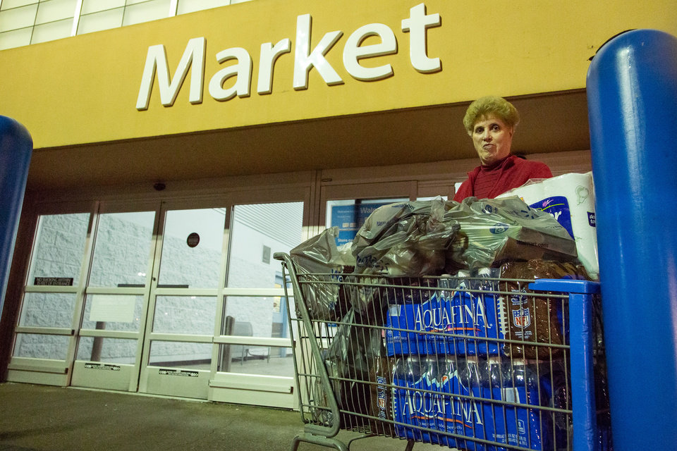 Photo - Dora Clark of Charleston, W.Va. stocks up on bottled water at a supermarket in Charleston, W.Va. on Saturday, Jan. 11, 2014 in the wake of Freedom Industries' chemical spill into the Elk River on Thursday. Customers were allowed to purchase up to four cases of water at a time. As many stores ran out, the West Virginia National Guard was sent to bring bottled water to local distribution centers. (AP Photo/Michael Switzer)