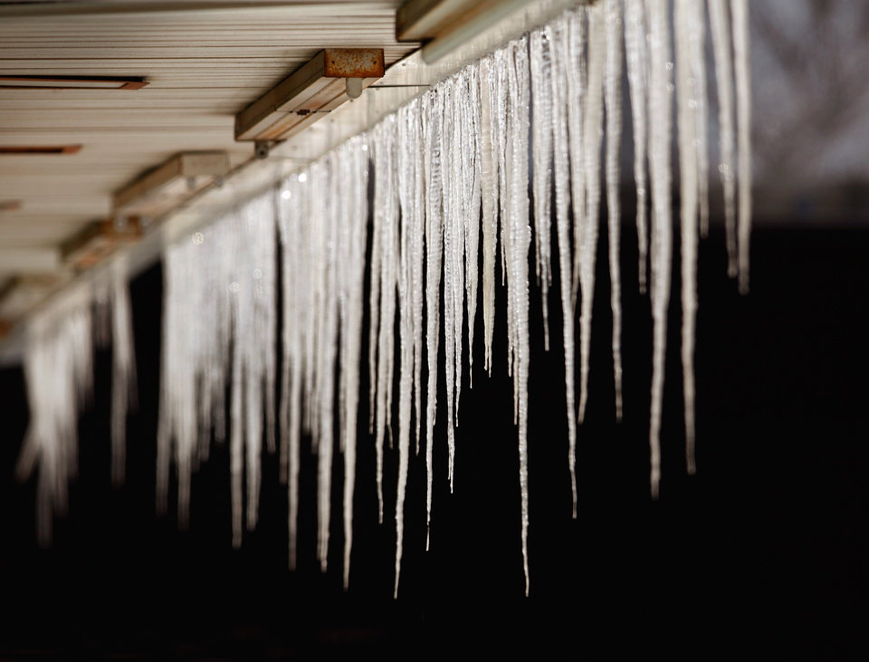 Photo - Icicles of varying lengths hang from an awning in front of  a row of small shops on NE 23rd Street near the state Capitol Thursday, Feb. 3, 2011. Photo by Jim Beckel, The Oklahoman