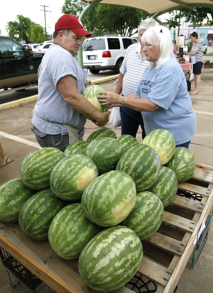 Photo -  Greg Loman, left, sells a watermelon to Mike and Jane Taylor during the Edmond Farmers Market at Festival Market Place. PHOTO BY PAUL HELLSTERN, THE OKLAHOMAN   PAUL HELLSTERN -