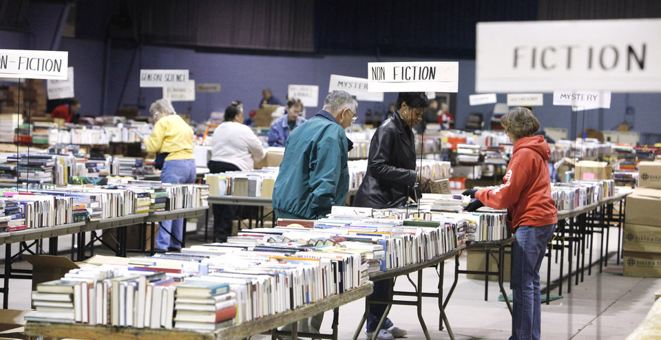 Volunteers stack books on tables for the annual Friends of the Library Book Sale.  PHOTO BY PAUL B. SOUTHERLAND, THE OKLAHOMAN