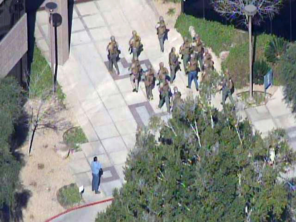 This frame grab provided by abc15.com shows the scene at a Phoenix office complex where police say a gunman shot at least three people on Wednesday, Jan. 30, 2013. Officer James Holmes said the victims were taken to hospitals and did not know if their injuries were life threatening. (AP Photo/abc15.com) MANDATORY CREDIT