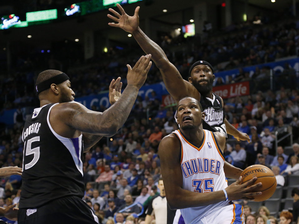 Photo - Oklahoma City Thunder forward Kevin Durant (35) drives past Sacramento Kings forward Reggie Evans, rear, and center DeMarcus Cousins (15) during the third quarter of an NBA basketball game in Oklahoma City, Friday, March 28, 2014. Oklahoma City won 94-81. (AP Photo/Sue Ogrocki)