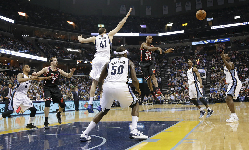Photo - Miami Heat guard Ray Allen (34) passes away from Memphis Grizzlies defenders Kosta Koufos (41) and Zach Randolph (50) in the first half of an NBA basketball game Wednesday, April 9, 2014, in Memphis, Tenn. (AP Photo/Mark Humphrey)