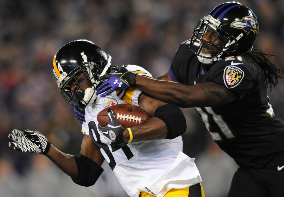Photo - Pittsburgh Steelers wide receiver Antonio Brown, left, is tackled by Baltimore Ravens cornerback Lardarius Webb after getting a first down in the first half of an NFL football game on Thursday, Nov. 28, 2013, in Baltimore. (AP Photo/Gail Burton)